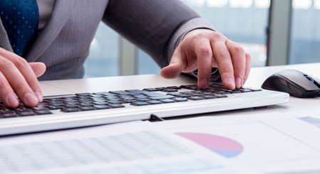 Foto de Finance professional working on keyboard with reports - Imagen libre de derechos