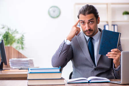 Photo pour Young male businessman reading books at workplace - image libre de droit
