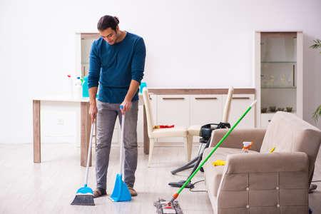 Photo pour Young man husband doing housework at home - image libre de droit