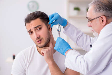Photo for Young man visiting experienced doctor dermatologist - Royalty Free Image