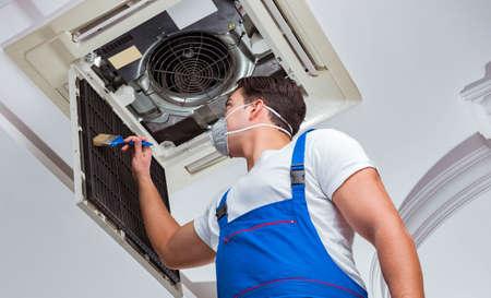 Photo pour Worker repairing ceiling air conditioning unit - image libre de droit