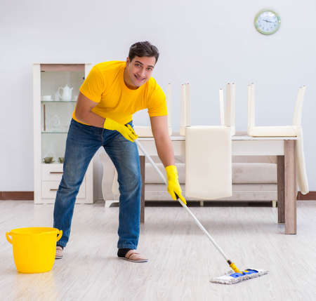 Photo pour Young man doing chores at home - image libre de droit