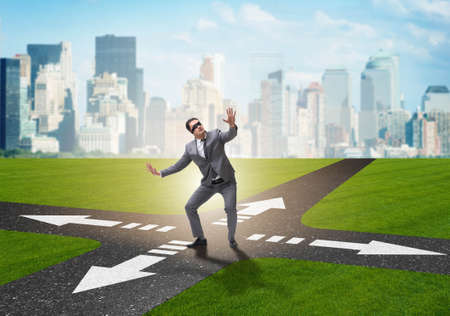 Photo pour Young businessman at crossroads in uncertainty concept - image libre de droit