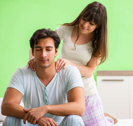 Photo pour Woman doing massage to her husband in bedroom - image libre de droit