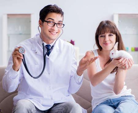 Photo pour Woman with pet rabbit visiting vet doctor - image libre de droit