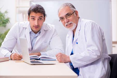 Photo pour Experienced doctor teaching young male assistant - image libre de droit