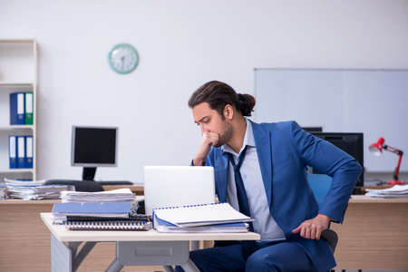 Photo for Young male employee unhappy with excessive work - Royalty Free Image