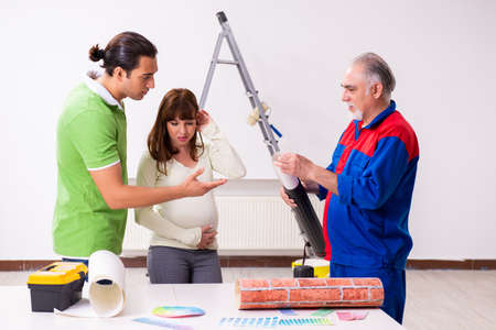 Photo for Young couple and old contractor in home renovation concept - Royalty Free Image