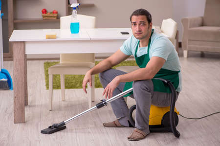 Photo pour Young male contractor cleaning the house - image libre de droit