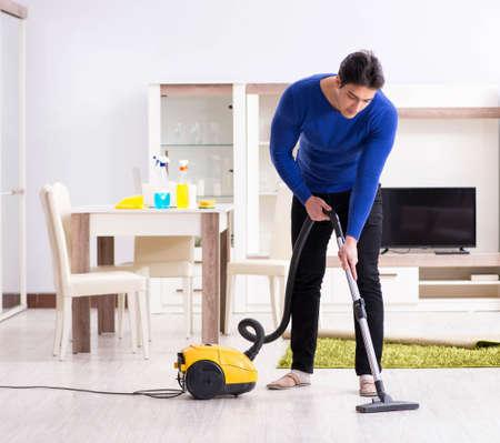 Photo pour Young man vacuum cleaning his apartment - image libre de droit