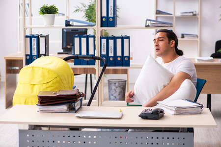 Photo pour Young male employee looking after newborn at workplace - image libre de droit