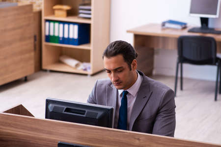 Photo pour Young male employee unhappy with excessive work in the office - image libre de droit