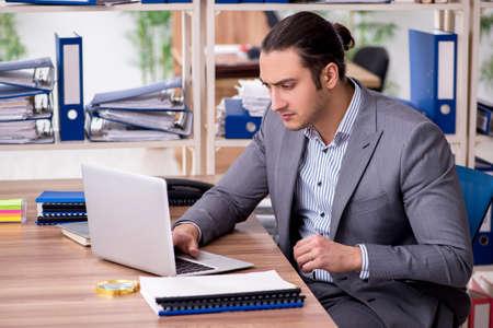 Foto de Young male employee businessman at workplace - Imagen libre de derechos
