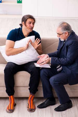 Photo pour Young man visiting old male psychologist - image libre de droit