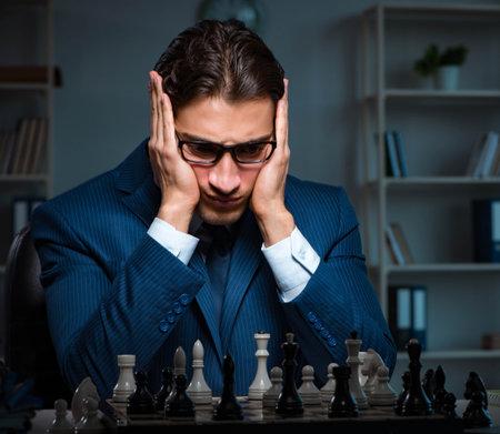 Photo pour Businessman playing chess in strategy concept - image libre de droit