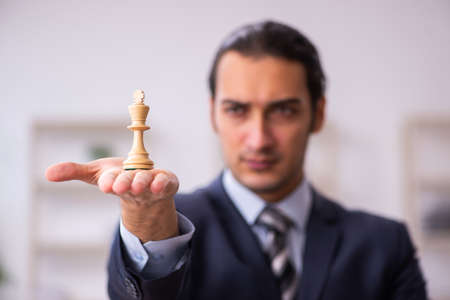 Photo pour Young male employee playing chess at workplace - image libre de droit