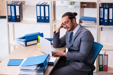 Photo pour Young male employee and too much work in the office - image libre de droit