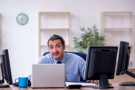 Photo pour Young male employee working in the office - image libre de droit