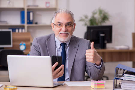 Photo pour Old male employee working in the office - image libre de droit