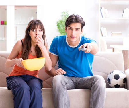 Photo pour Young man watching football with his wife at home - image libre de droit