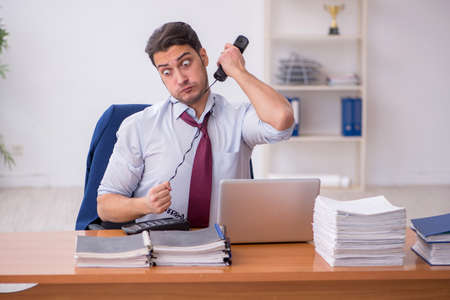 Photo pour Young businessman and too much work in the office - image libre de droit