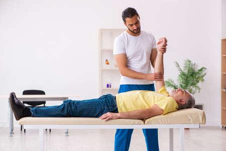 Photo pour Old male patient visiting young male doctor chiropractor - image libre de droit