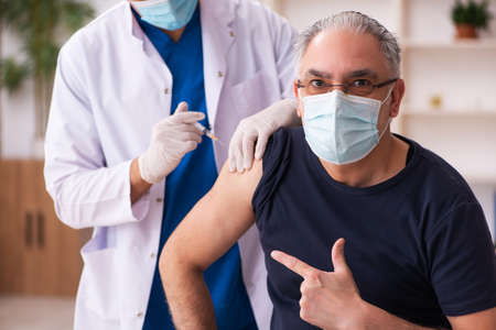 Photo pour Old man visiting young doctor in vaccination concept - image libre de droit