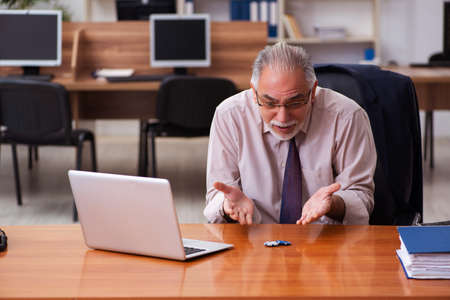 Photo pour Old male employee in gambling concept at workplace - image libre de droit