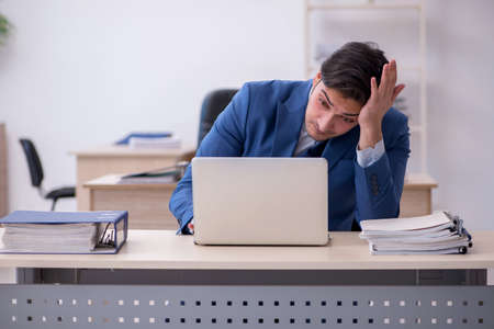 Photo for Young male employee being unhappy with excessive work - Royalty Free Image