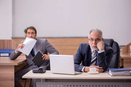 Photo pour Old boss and young male assistant in the office - image libre de droit