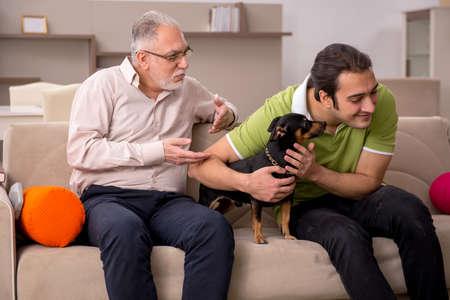 Photo pour Two men with dog at home - image libre de droit
