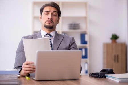 Foto de Young attractive male employee sitting at workplace - Imagen libre de derechos