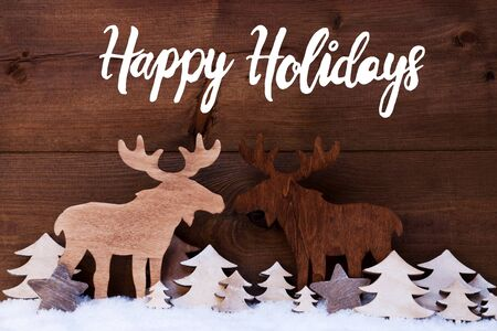 Photo pour English Calligraphy Happy Holidays. White Wooden Tree And Moose On Snow WIth Wooden Background - image libre de droit
