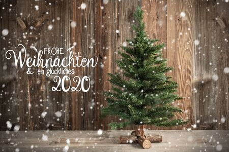 Photo pour German Calligraphy Frohe Weihnachten Und Ein Glueckliches 2020 Means Merry Christmas And Happy New Year 2020. Christmas Tree Infront Of Brown Rustic Wooden Background With Snow - image libre de droit