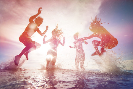 Foto de Silhouettes of happy young people jumping in sea at the beach on summer sunset - Imagen libre de derechos