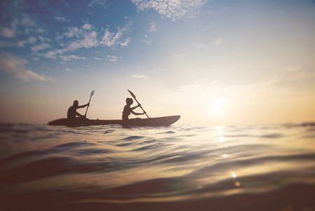 Photo pour silhouette of a couple on a boat in the sea at sunset - image libre de droit