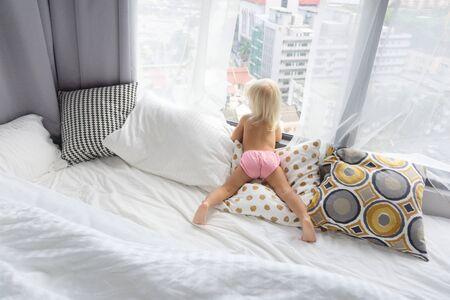 Foto de child looks out the window in the big city - Imagen libre de derechos