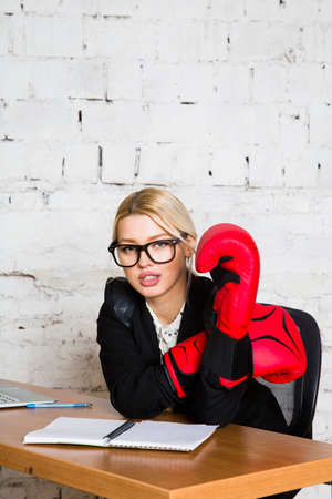 Young blond beauty businesswoman sitting at a office table with laptop, notebook and glasses in suit and boxing gloves.