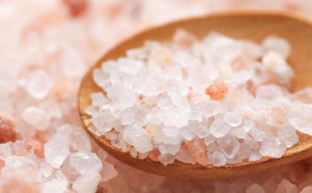Pink Himalayan salt. Himalayan salt batteries. Pink crystal salt in wooden spoon. Close up of Himalayan salt - pink and orange coarse crystals.