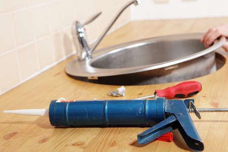 Caulking gun with silicone sealant against kitchen sink installation process
