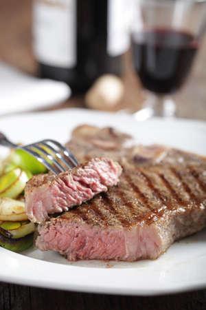 Medium rare T-bone steak with roasted leek and red wine