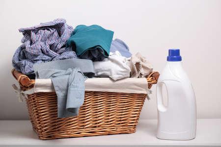 Photo pour Dirty clothes in the laundry basket and a bottle of detergent - image libre de droit