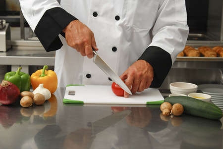 A chef cutting fresh vegetables in a restaurant kitchen.