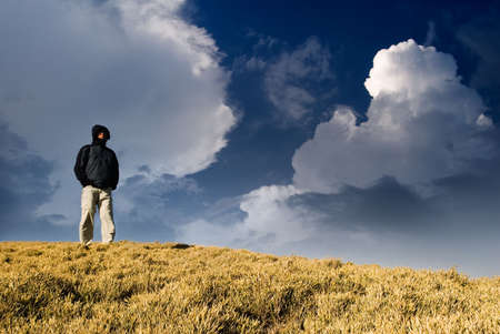One man standing on the hill and watch somewhere far away.