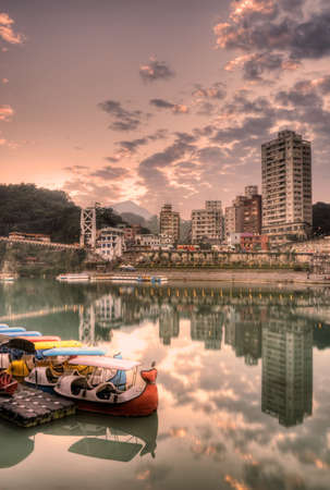 Colorful boats on river with buildings and bridge in sunset.