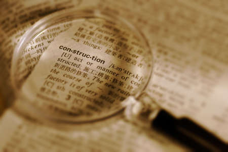 Focus on construction word by magnifier in book.