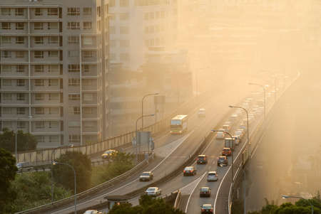 Air pollution scenic with cars on highway and yellow smoke in city.