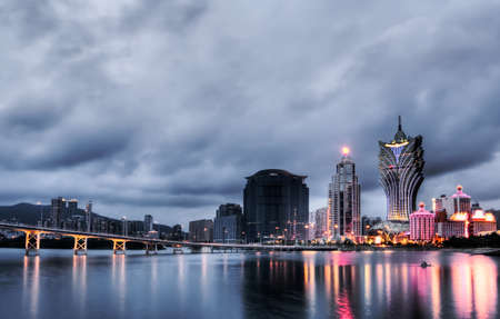 Macao cityscape with famous landmark of casino skyscraper and bridge in night.