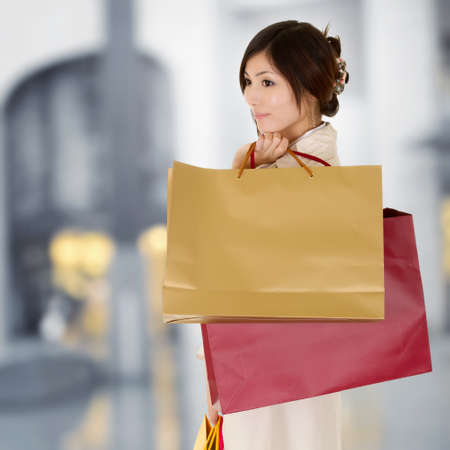 Modern woman shopping in mall holding bags and thinking.