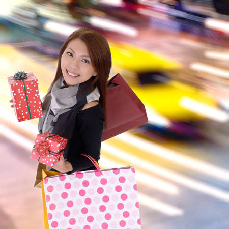 Happy shopping woman in modern colorful city night with cars motion blurred.